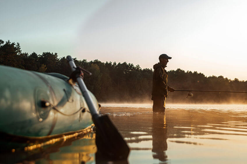 inflatable boat on the lake at dawn and fisherman fishing