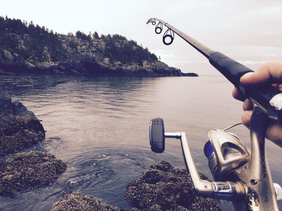 man casting fishing rod with spinning reel on river