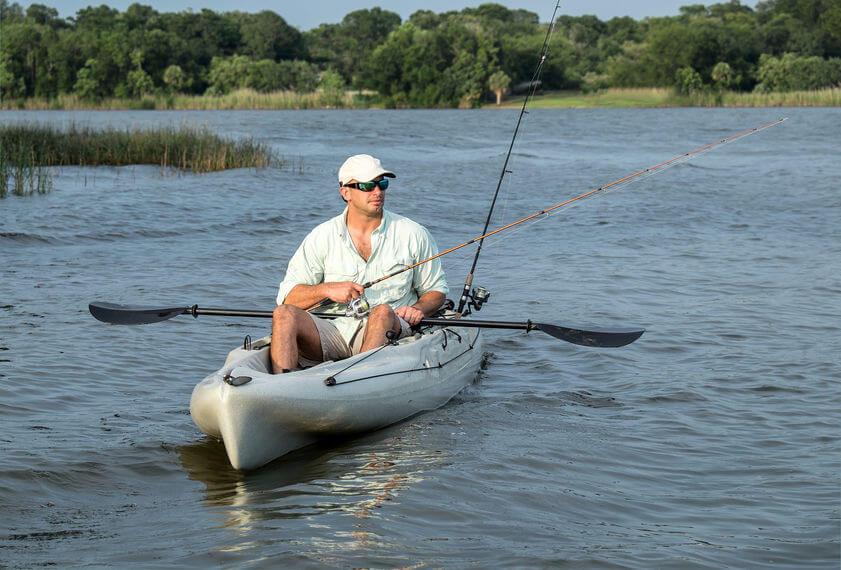 man enjoys fishing from kayak