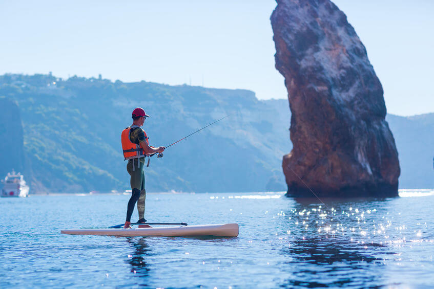 man fishing from stand up paddle board in ocean
