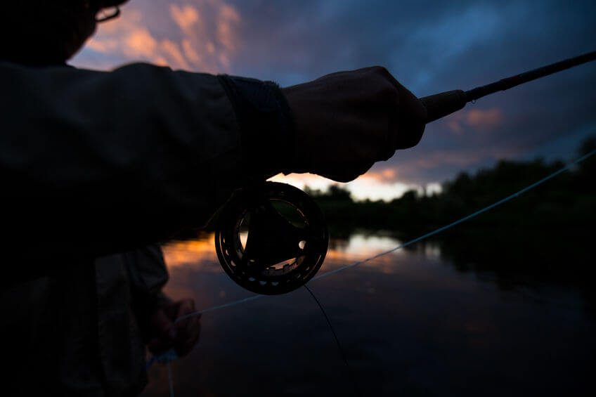man fishing in river with fly rod from kayak