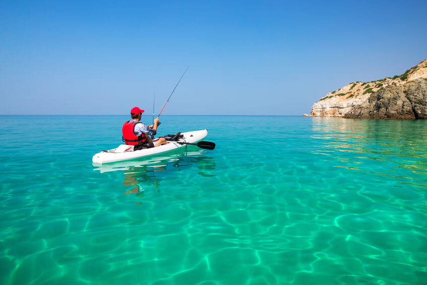 man fishing on a sit-on-top kayak in the sea with clear water