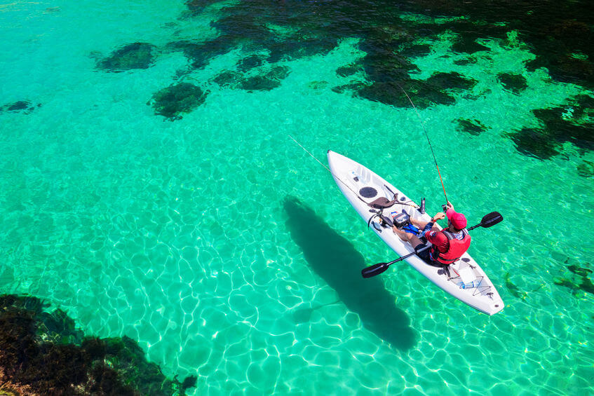 man fishing on a stand up kayak in the sea