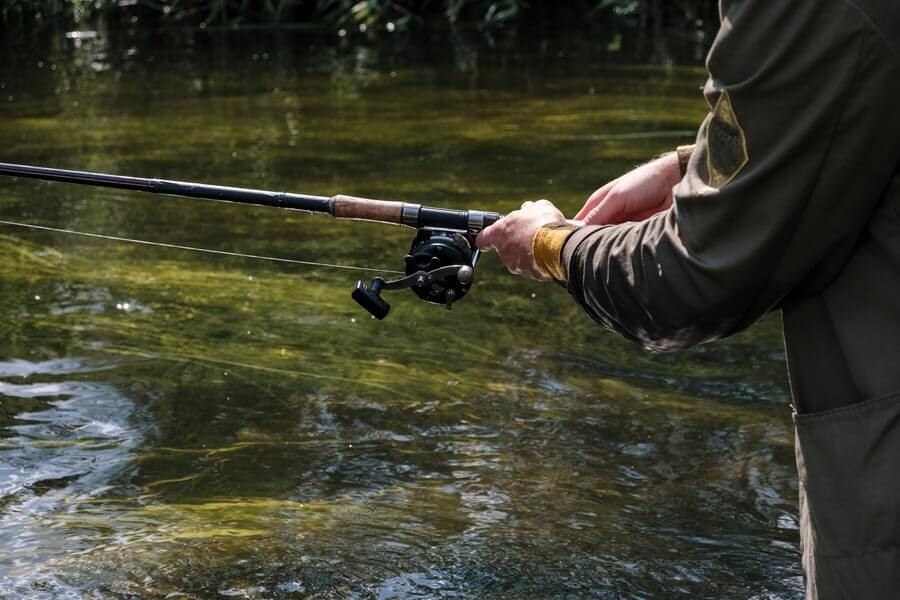 man fishing using baitcasting reel