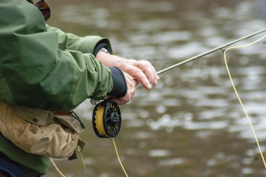 man fly fishing in river holding fly rod with reel