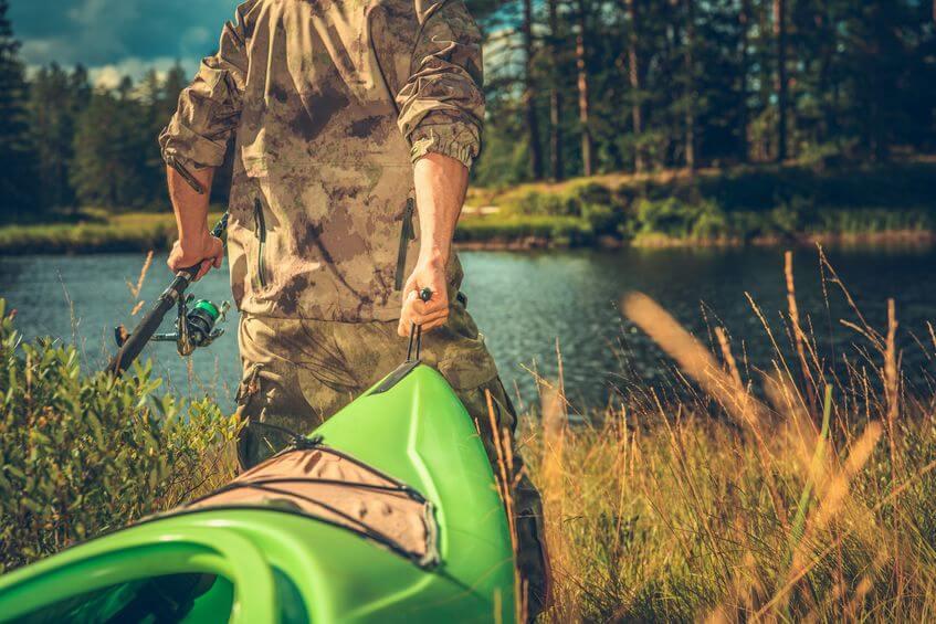 man going fishing with kayak and telescopic fishing rod
