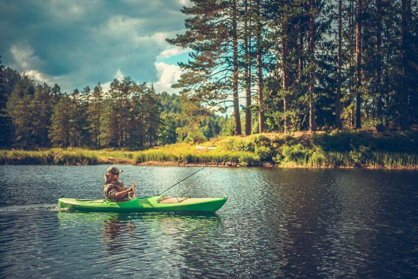 man holding fishing rod and fishing from a kayak on the lake