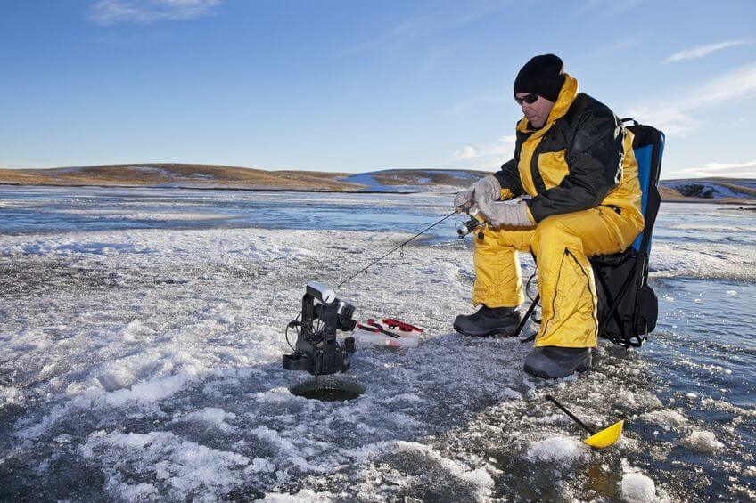man ice fishing on a frozen lake