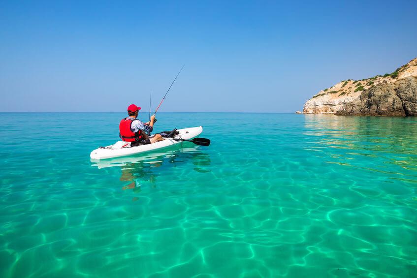 man in white kayak fishing