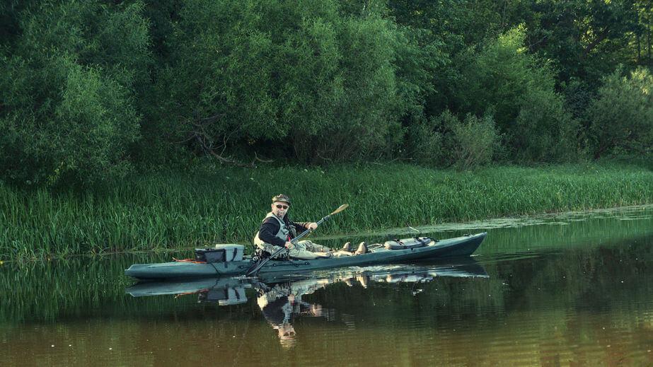 man kayak fishing in river