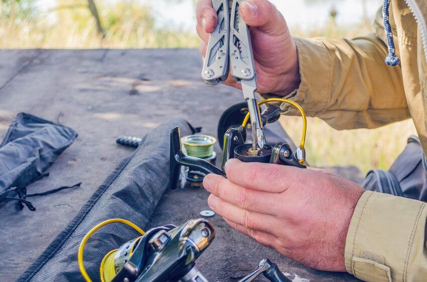 man repairs a fishing spinning reel