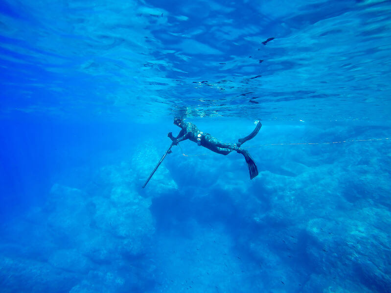 man spearfishing in ocean