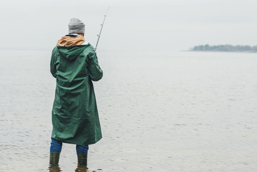 man wearing green raincoat jacket and fishing on rainy autumn day