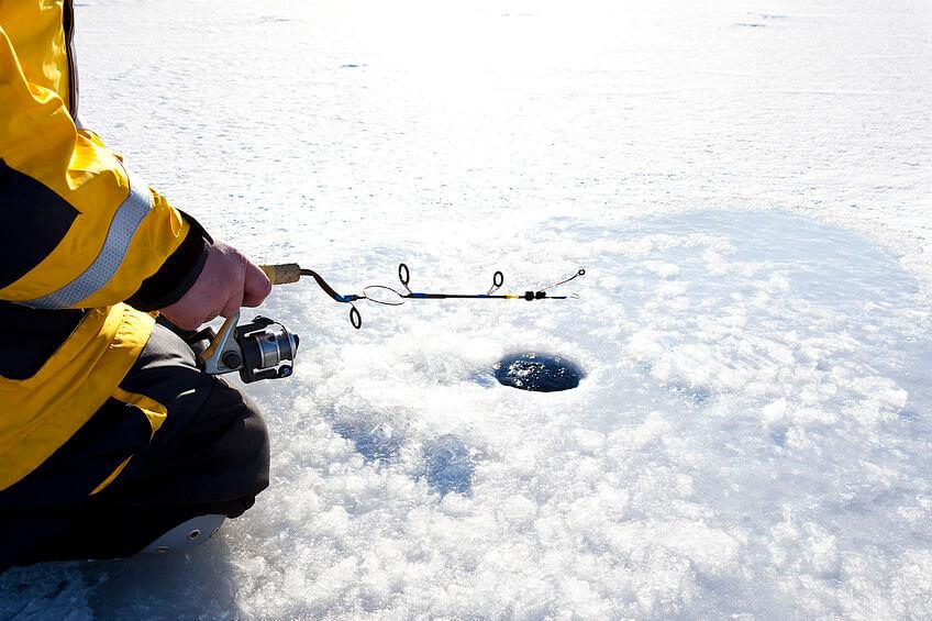 man wearing ice fishing bibs and jacket fishing on frozen lake