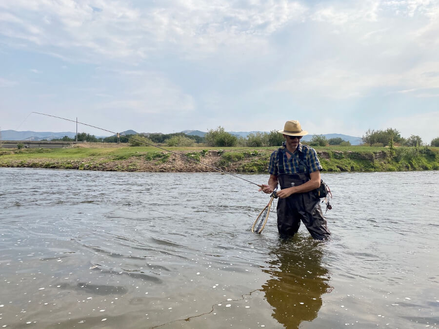 man wearing waders and fly fishing in river