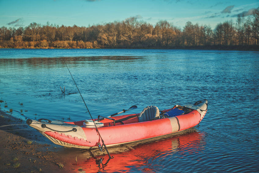 red inflatable fishing kayak on the autumn river and fishing rod
