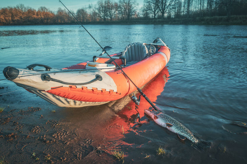 red inflatable fishing kayak on the autumn river