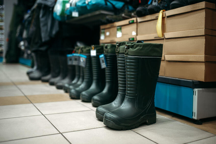 row of rubber fishing deck boots in fishing shop