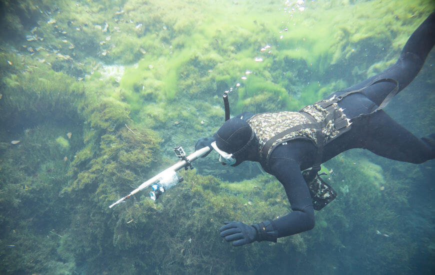 spearfishing man with flashlight in deep of lake swimming with speargun
