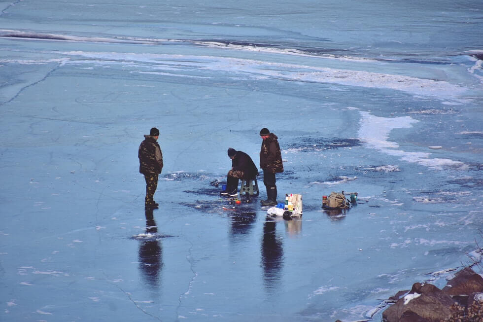 three anglers ice fishing on frozen lake