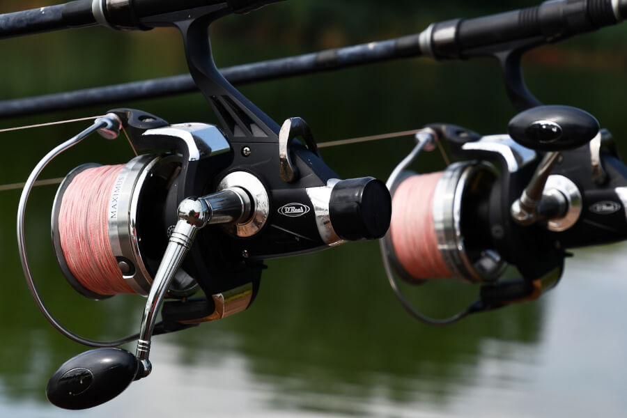 two fishing reels with red fishing line