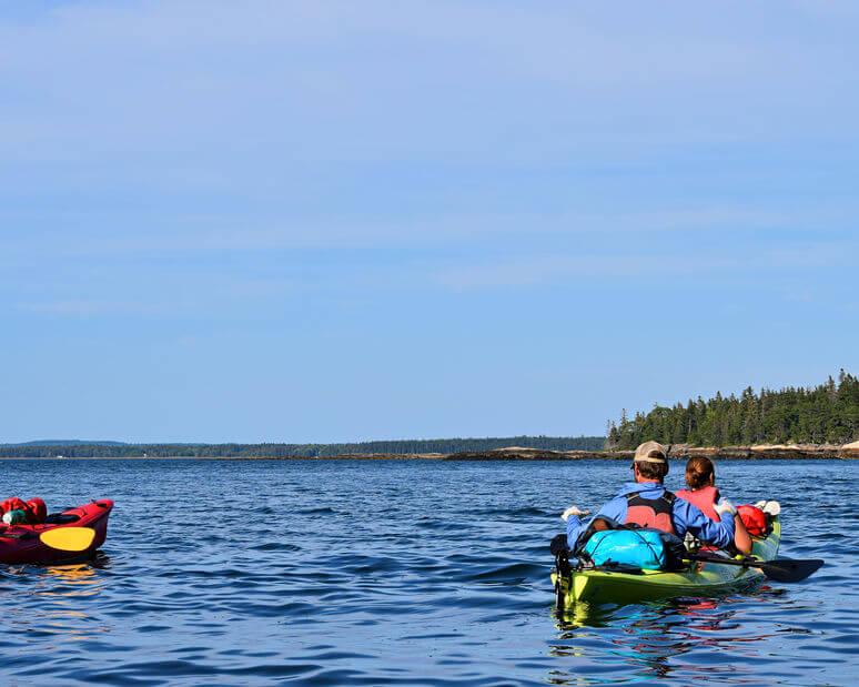 two kayakers in tandem fishing kayak at lake