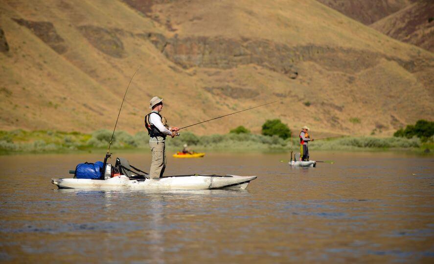 two men fishing from kayak in river