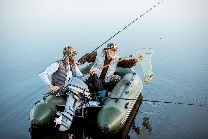 two men fishing on the inflatable boat on the lake