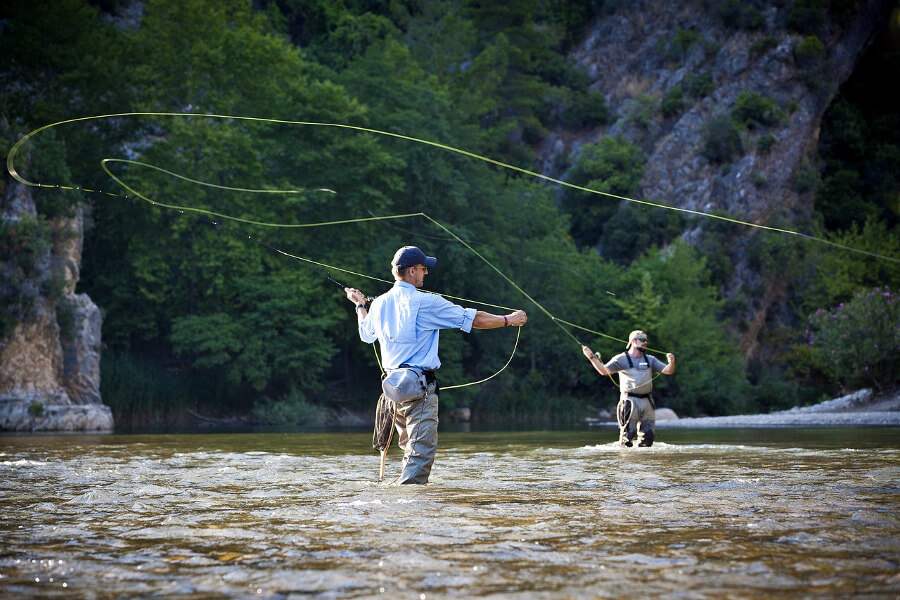 two men fly fishing in river