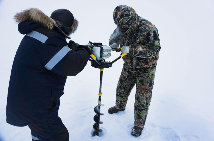 two men on a winter fishing drill hole with electric ice auger