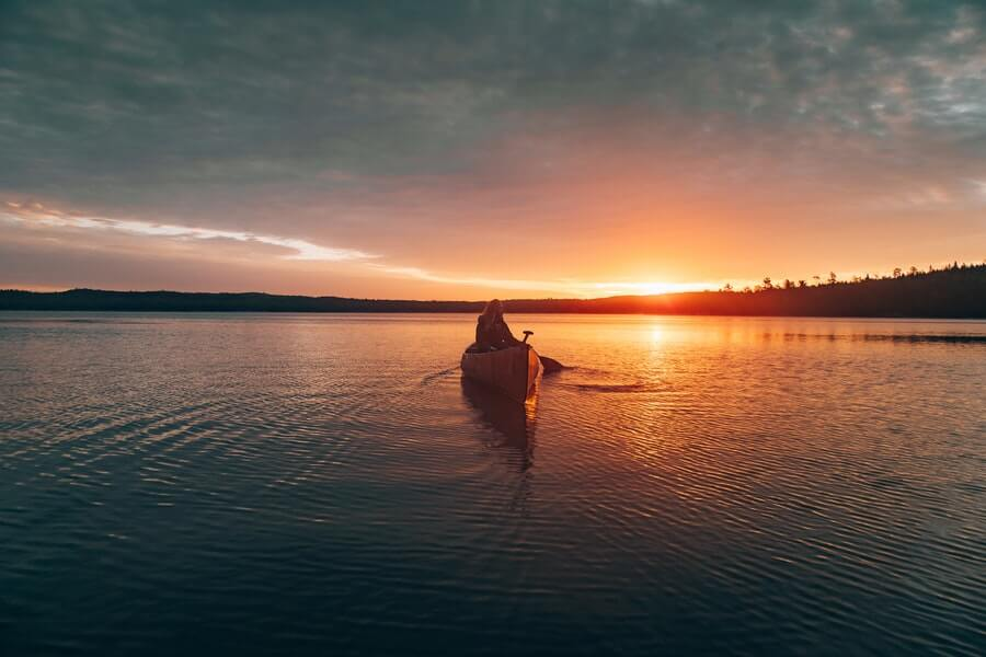 woman in canoe at sunset